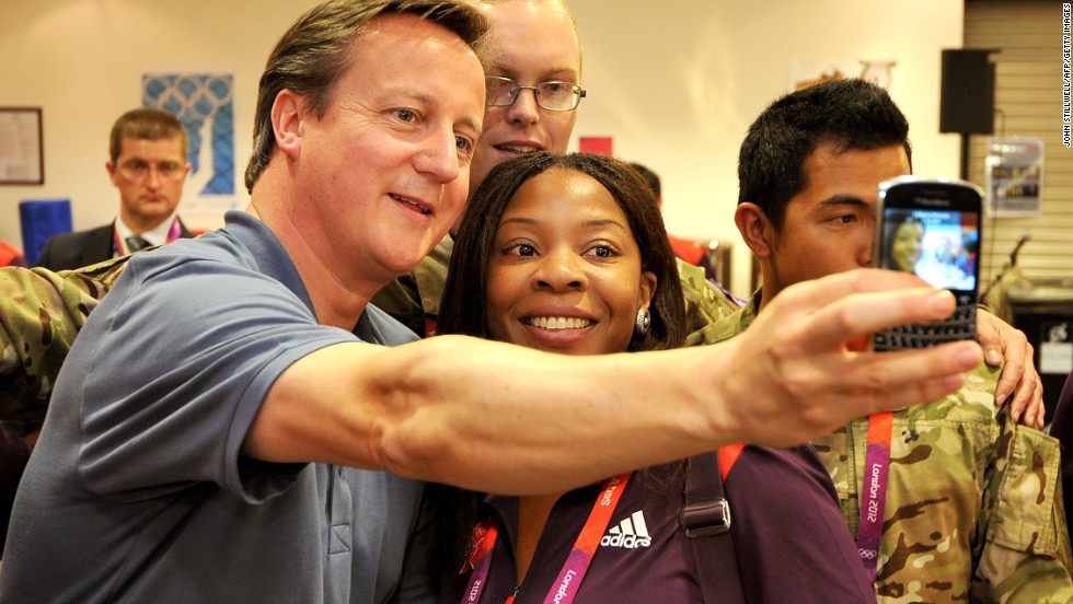 Even political figures are getting in on the trend. Here, British Prime Minister David Cameron takes a photograph with Olympic volunteer Anita Akuwudike in London.