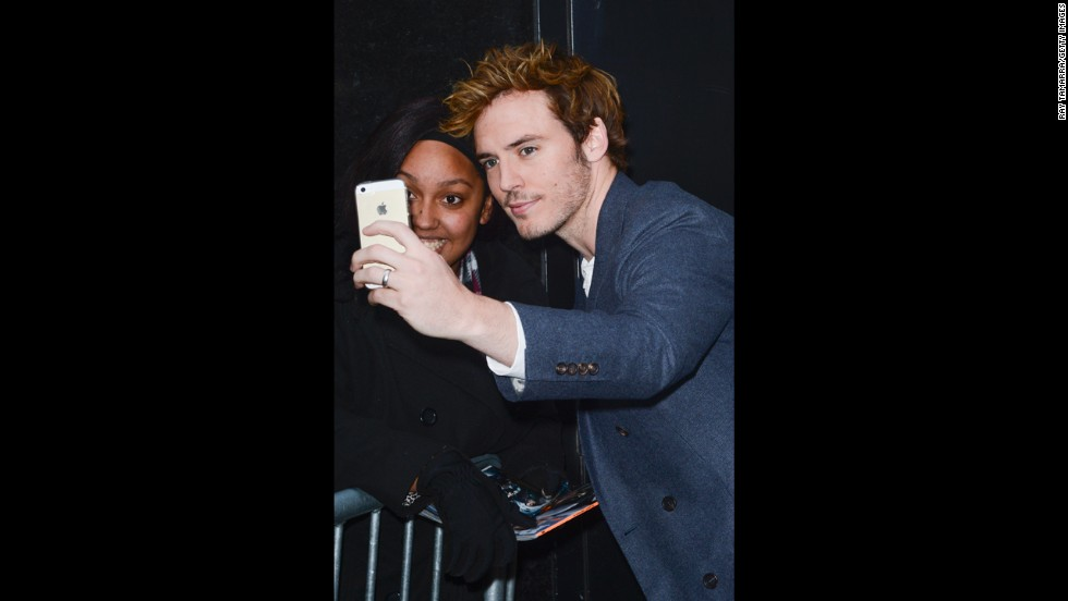 Actor Sam Claflin poses for photos with fans in New York City.