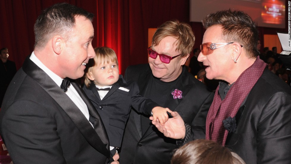 John, partner David Furnish and their son, Zachary, talk with singer Bono, right, at an Academy Awards viewing party in February 2013. John and Furnish have since welcomed a second son, Elijah.