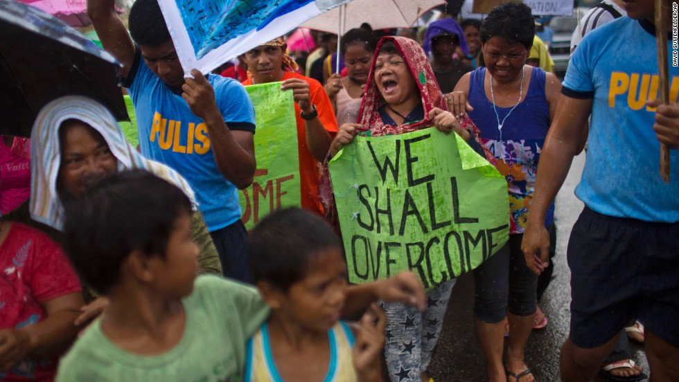 People in Tacloban march in the rain November 19 during a procession calling for courage and resilience among survivors.