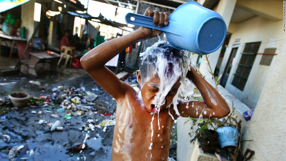 "NOVEMBER 19 - TACLOBAN, PHILIPPINES: A young boy takes a shower at a school which has been turned into a temporary shelter in Tacloban. Nearly 4,000 people died and <a href=""http://edition.cnn.com/2013/11/09/world/iyw-how-to-help-typhoon-haiyan/index.html?hpt=hp_t2"">hundreds of thousands were displaced by Typhoon Haiyan</a>, which tore across several islands in the eastern Philippines on November 8."