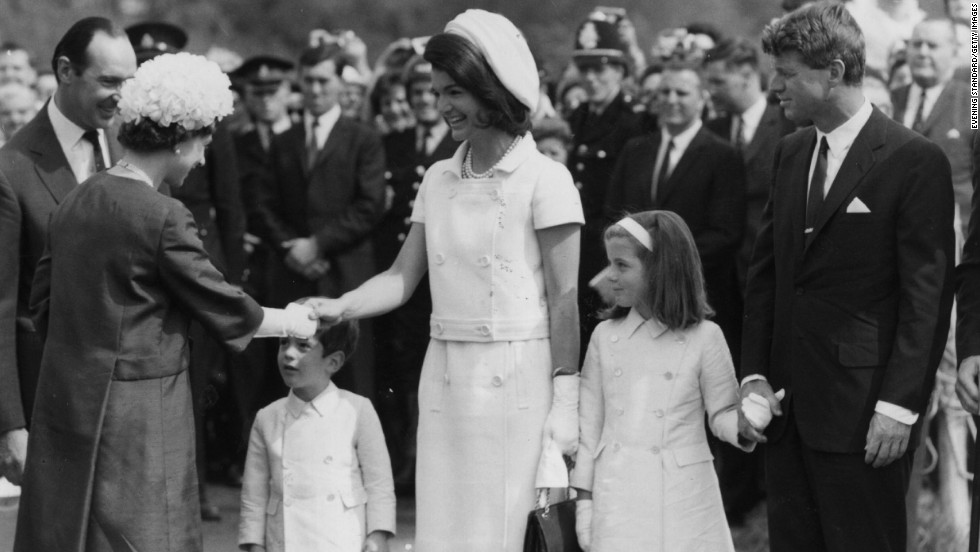 Caroline, alongside her mother and uncle Robert Kennedy, greet Queen Elizabeth II in London in 1965.