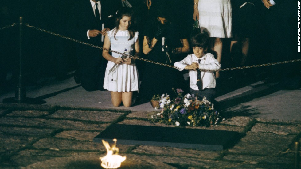 Caroline kneels beside her mother and brother at her father's grave in 1968.