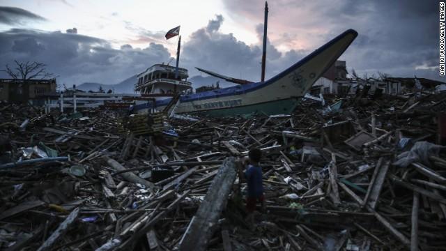 A boy climbs across debris in Tacloban on November 20.