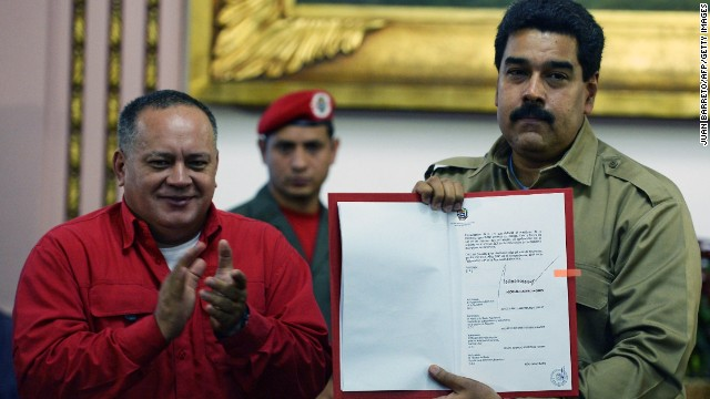 The president of the Venezuelan National Assembly, Diosdado Cabello, applauds Wednesday as Venezuelan President Nicolas Maduro shows the document giving him special decree powers.