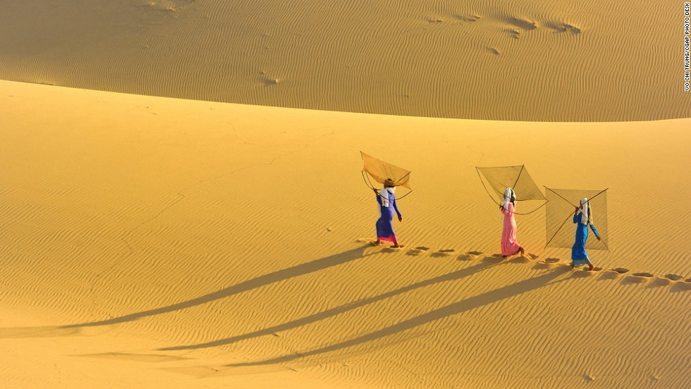 A group of Vietnamese women cross the sand dunes to the beach to go fishing.