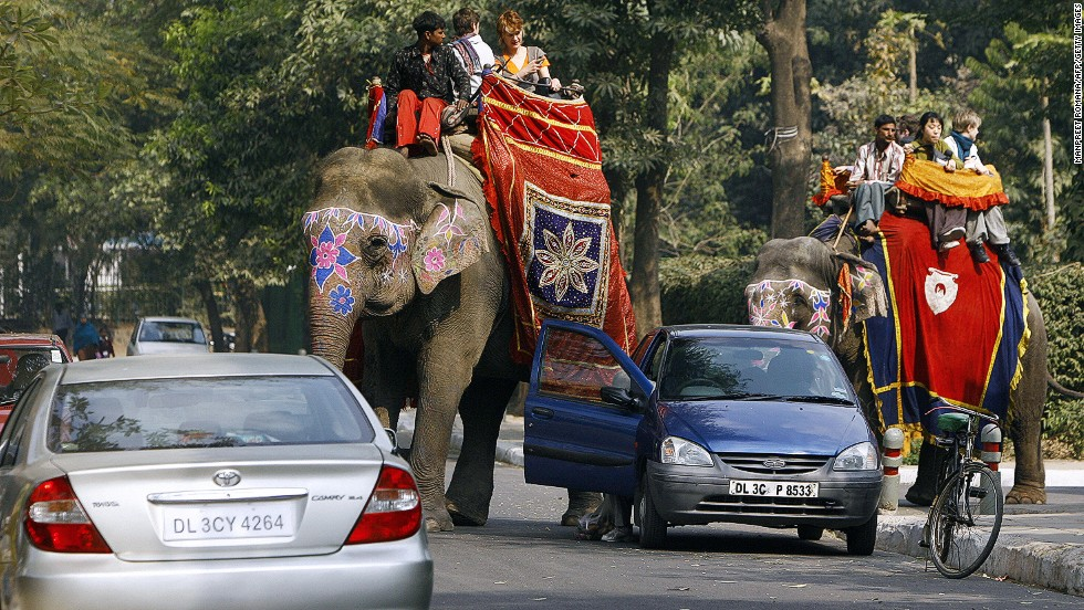 Twenty reasons to take a vacation: Riding an elephant in the chaos of Indian traffic may be nerve-racking, but it's still better than sitting on the couch flicking channels.