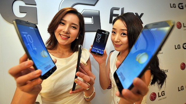 """South Korean models show LG Electronics' curved-screen smartphone """"G Flex"""" during a media event to unveil the new product at the company's headquarters in Seoul on November 5, 2013. The G Flex has a 6-inch plastic OLED display that curves inward from top and bottom. The device will hit the market in South Korea next week. AFP PHOTO / JUNG YEON-JEJUNG YEON-JE/AFP/Getty Images"""