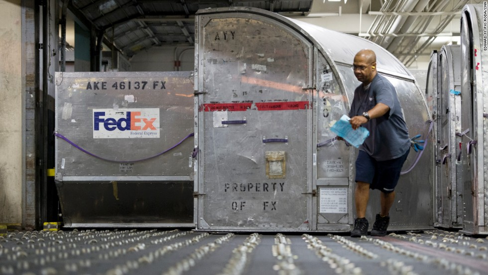 A FedEx worker moves containers full of packages at the cargo facility.