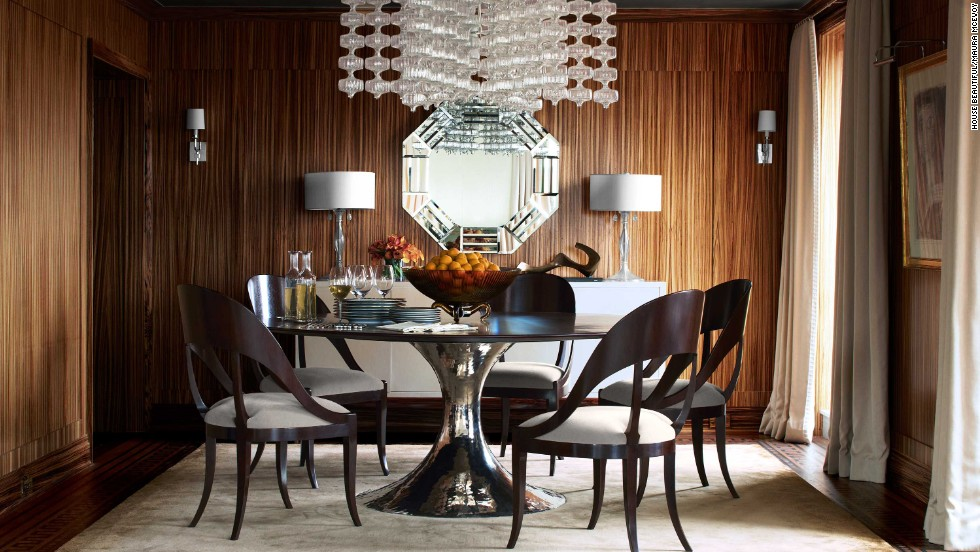 This dining room by Phoebe and Jim Howard, featured in the November 2013 issue of House Beautiful, sets modern-style furniture against moody wood walls.