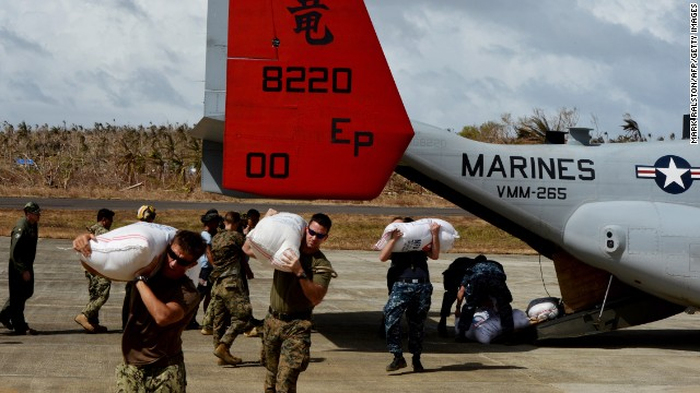 U.S. servicemen unload relief supplies from a Marines Osprey aircraft at Guiuan Airport on November 21.