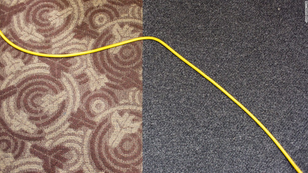 A floor cleaner's power cable crosses the carpet.