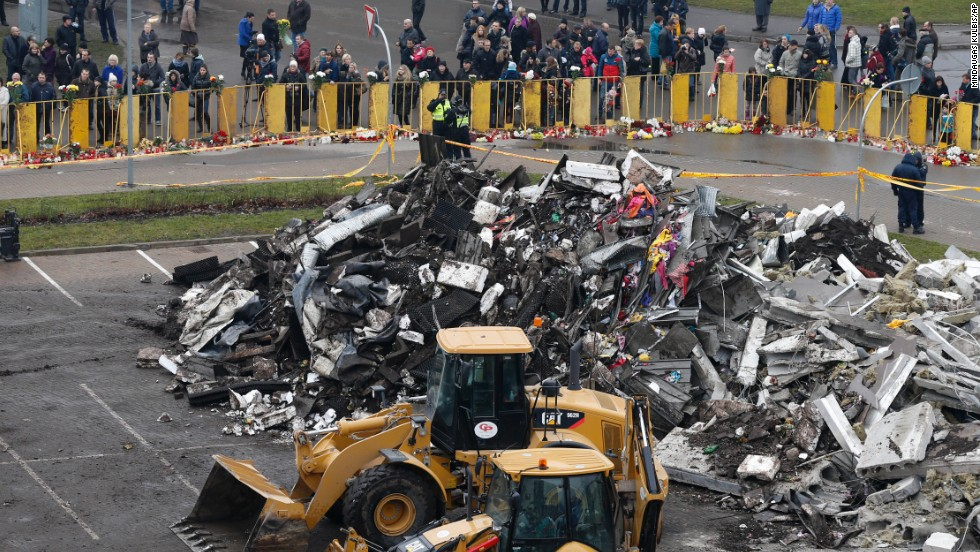 Debris piles up while people put flowers and light candles in front of the supermarket on November 23. The collapse was the Baltic state's deadliest accident since its independence from the Soviet Union in 1991, local media reported.