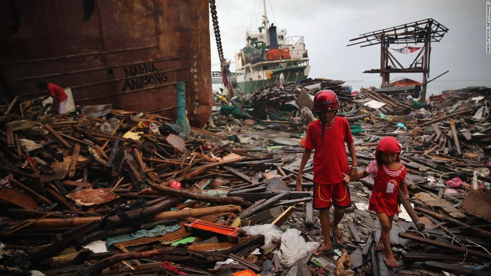 Children walk through debris near the shoreline where several tankers ran aground on November 23, in Leyte, Philippines.