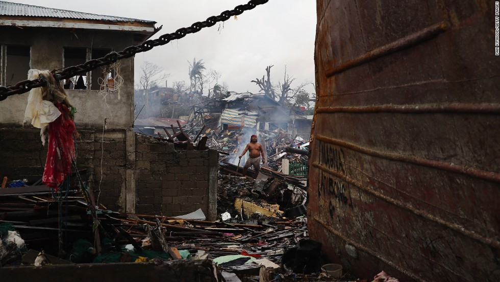 A man clears debris from in front of his home near the shoreline on November 23 in Leyte.