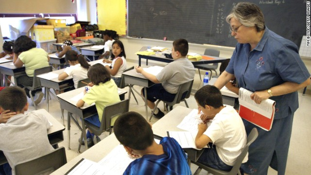 A teacher assists third-grade students in a Chicago classroom. Illinois is one of 45 states that have adopted Common Core educational standards.
