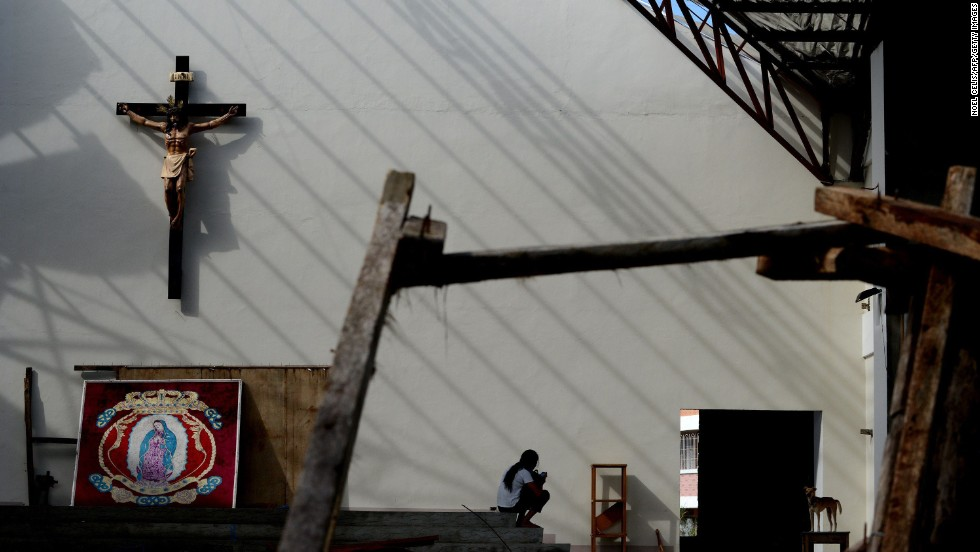 A woman rests inside the damaged Our Lady of Guadalupe shrine in Tacloban, Philippines, on Sunday, November 24.