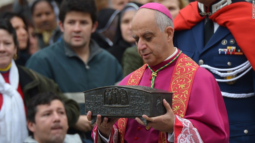 Italian archbishop Rino Fisichella holds the ashes of St Peter before a ceremony of Solemnity of Our Lord Jesus Christ the King at St Peter's square on November 24, 2013 at the Vatican.