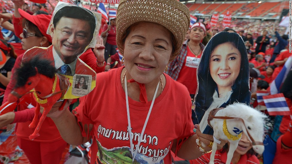 Thai pro-government 'red shirts' hold pictures of Thaksin and Yingluck Shinawatra as she gather at Rajamangala Stadium in Bankok Sunday.
