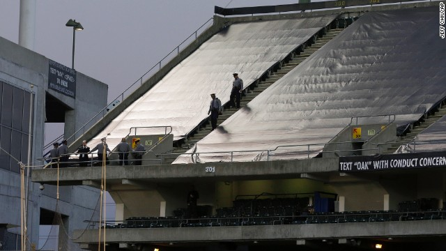 Authorities walk the upper deck of O.co Coliseum after, authorities say, a football fan jumped from the third deck.