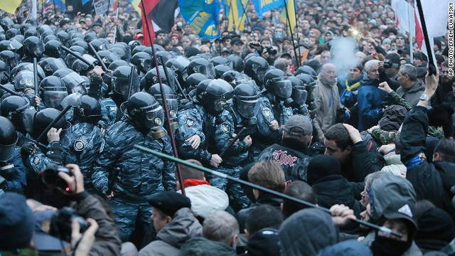 Opposition protesters and riot police clash in front of the Ukrainian Cabinet of Ministers in Kiev, Ukraine, Sunday, Nov. 24, 2013.