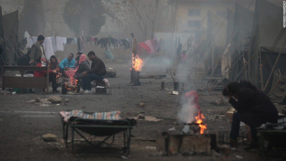Syrian refugees warm themselves near open fires at a refugee camp in Harmanli on Thursday, November 21.