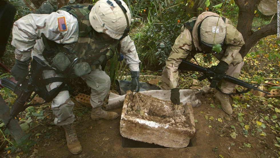 Two U.S. soldiers show the hole where Hussein was captured.
