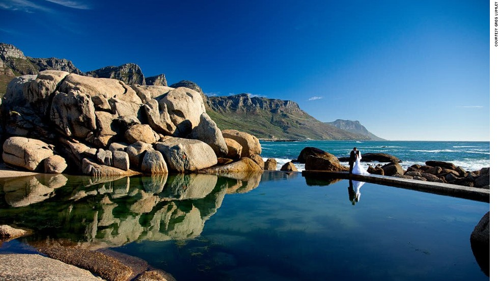 "Photographer Greg Lumley took this shot at a tidal pool in Cape Town after the ceremony and on the way to the reception. ""I had chosen this spot specifically because of the dramatic boulders and glass-like pool edging the ocean,"" says Lumley. ""The fact that the 12 Apostles -- part of Table Mountain -- were in the shot turned out to be total bonus, as I'd not noticed them before."""
