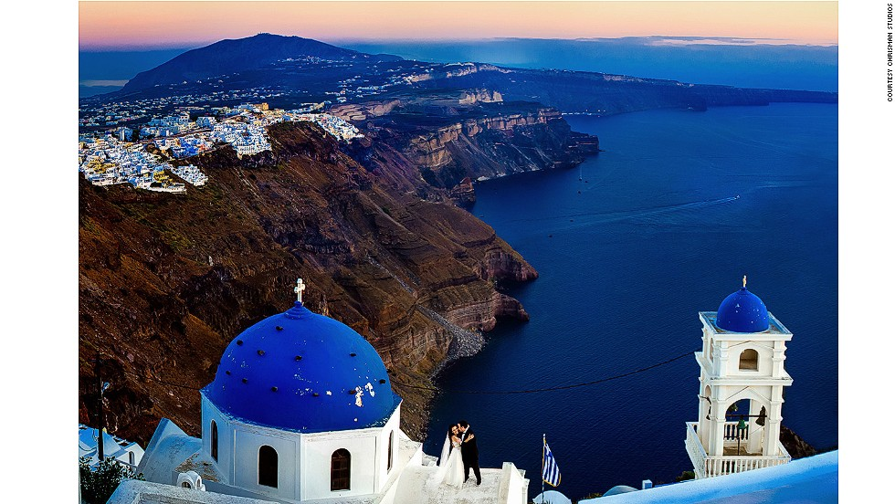 """""""As a photographer, when a couple is flying you across the world to such a picturesque location as Santorini, Greece, it's imperative to go home with at least one epic photo that shows the stunning backdrop of this ancient white and blue city,"""" says Chrisman. Mauricio Arias of Chrisman Studios posed his subjects and told them to keep interacting while he climbed high enough to capture the beautiful scene."""