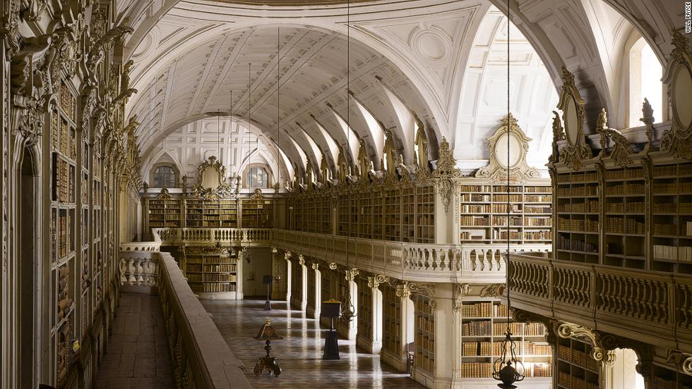 "<strong><br /><br />James Campbel</strong>l: ""The Mafra Palace Library in Mafra, Portugal is at 88 meters the longest Rococo monastic library in the world. Sadly the original designs are lost but we think it would have been covered in gold leaf with an ornate painted ceiling. However, because the construction lasted from 1717 to 1771, by the time it was completed a simplified decoration was adopted. The library also hosts a colony of bats who come out at night to feed on the insects who would otherwise eat the books."""