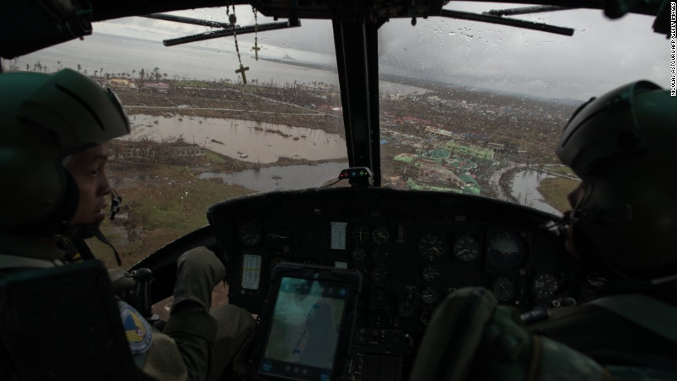 Philippines Air Force helicopter crewmen on Saturday, November 23, look at the damage to the town of Tacloban caused by Typhoon Haiyan.