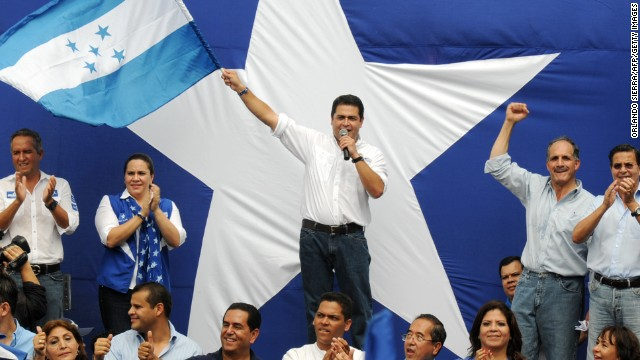 Juan Orlando Hernandez waves a flag after a march in support of the newly created Military Police in Tegucigalpa earlier this month.