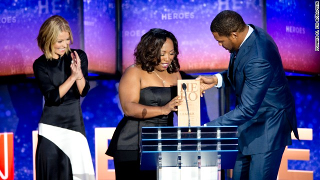 Kelly Ripa and Michael Strahan present the CNN Heroes award to Tawanda Jones on stage during the CNN Heroes award show.