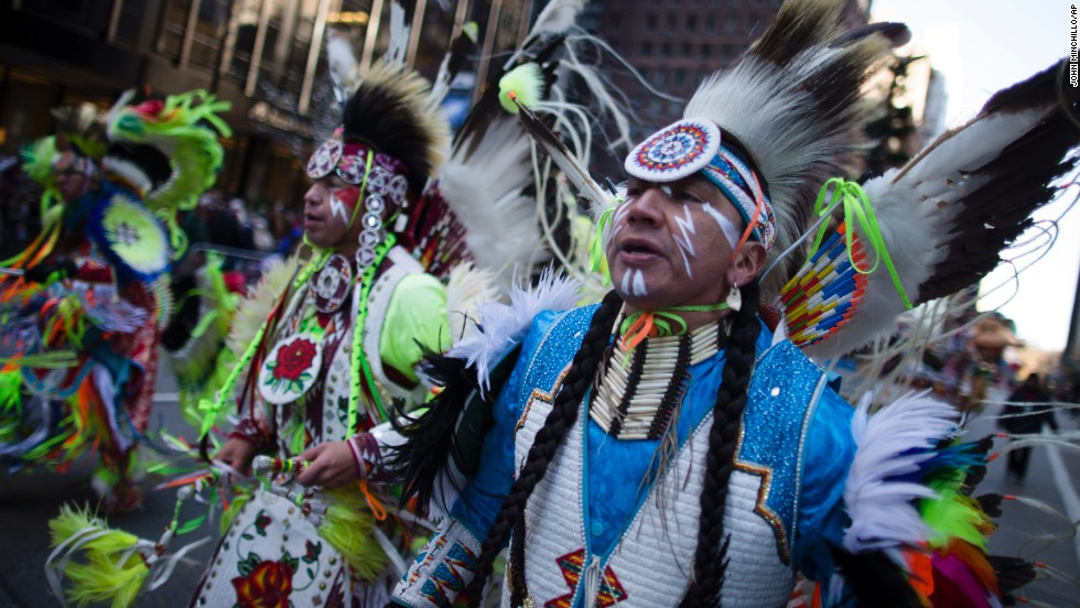 A Native American performance group marches down Sixth Avenue.