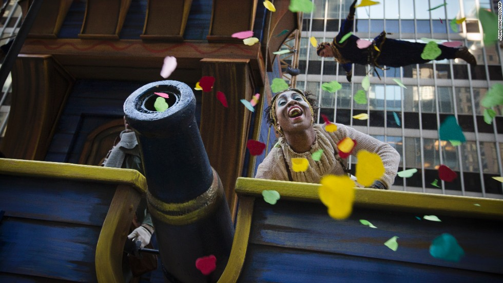 A performer on the Cirque du Soleil float fires confetti into the crowd.