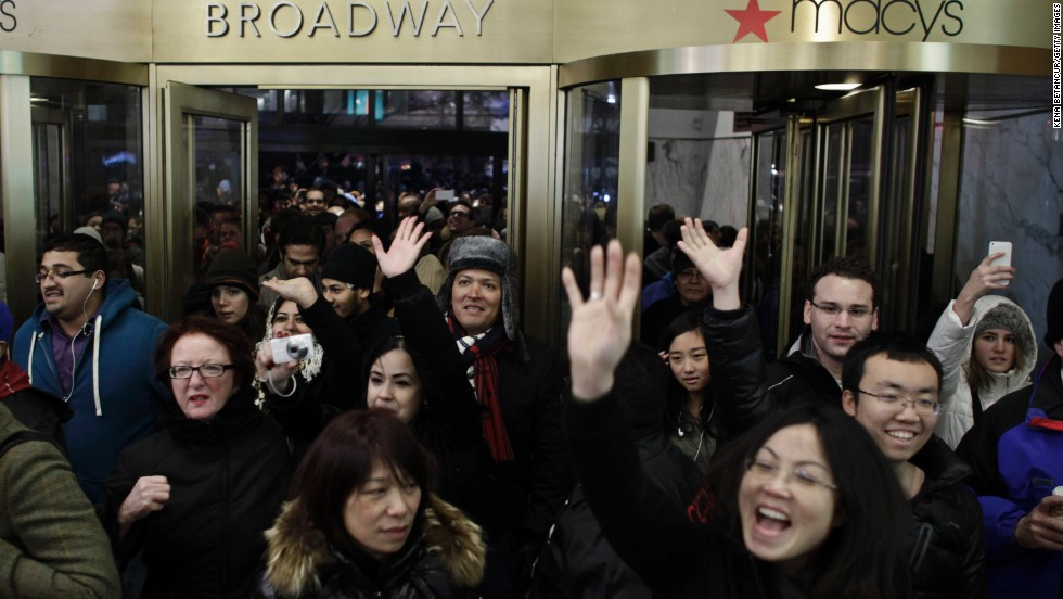 Shoppers enter Macy's as the New York store opens on Thanksgiving Day.