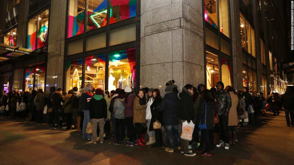 Shoppers stand in line on Fifth Avenue in New York as they wait for stores to open November 29.