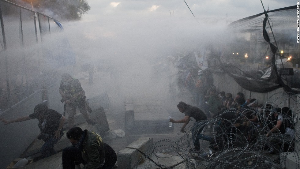 Anti-government protesters run for cover December 1 as police use tear gas and water cannons.
