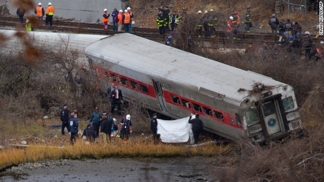 Viewed from Manhattan, first responders and others work at the scene of a  derailed Metro North passenger train in the Bronx borough of New York Dec. 1, 2013. The train derailed on a curved section of track in the Bronx early Sunday, coming to rest just inches from the water, killing at least four people and injuring more than 60, authorities said. Police divers searched the waters to make sure no passenger had been thrown in, as other emergency crews scoured the surrounding woods.