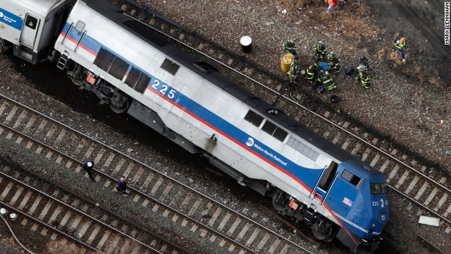 A Metro-North locomotive lies on its side after derailing, Sunday, Dec. 1, 2013 in the Bronx borough of New York. The train derailed on a curved section of track in the Bronx on Sunday morning, coming to rest just inches from the water and causing multiple fatalities and dozens of injuries, authorities said. (AP Photo/Mark Lennihan)