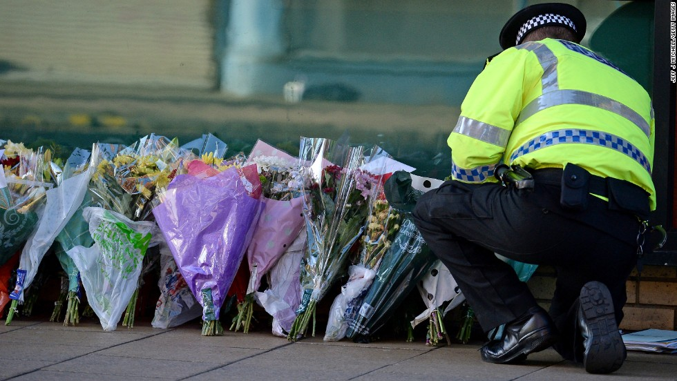 A police officer lays flowers new the pub on Sunday, December 1.