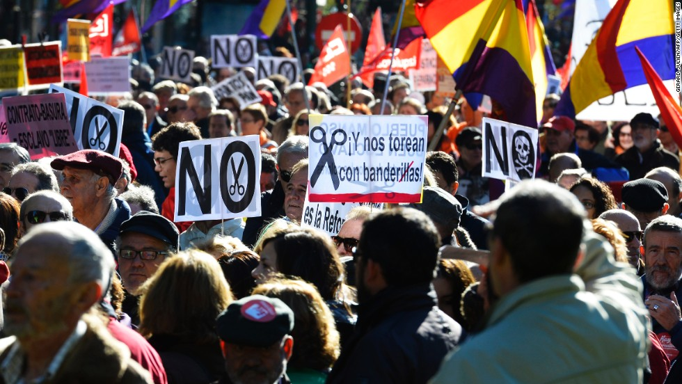 Demonstrators hold placards and flags of the Second Spanish Republic as they take part in a protest against the government's austerity measures in Madrid on November 23, 2013.
