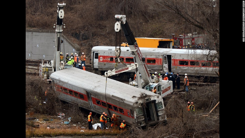 Cranes lift derailed train cars on Monday, December 2.