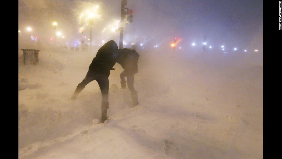 <strong>February 8:</strong> People shield themselves from snow as a blizzard arrives in the Back Bay neighborhood of Boston.
