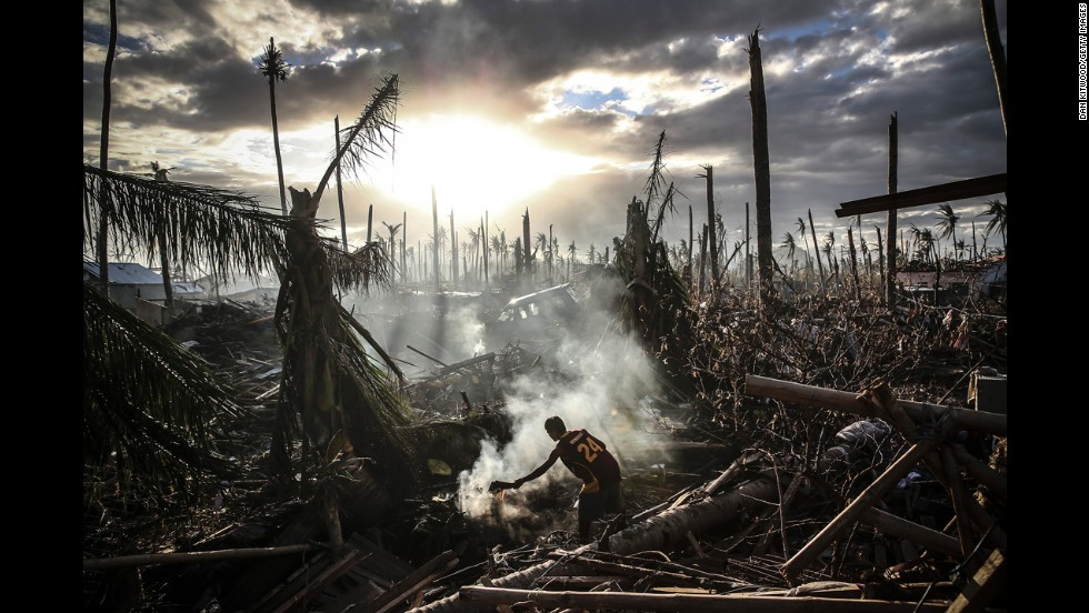 <strong>November 19:</strong> A man fans flames in Tanauan, Philippines, a week after Typhoon Haiyan ripped through the country. Haiyan, one of the strongest storms in recorded history, left thousands dead and many more homeless.
