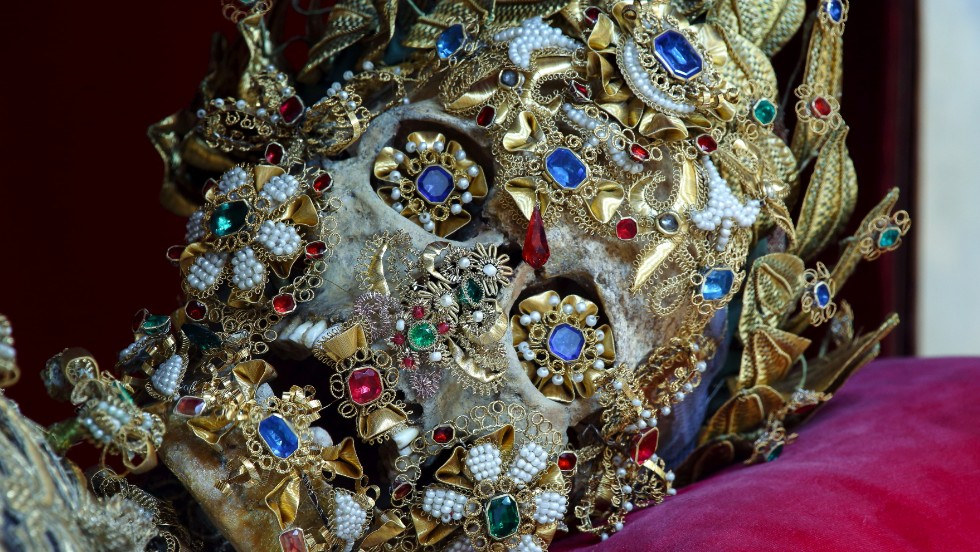 "<em>This St. Benedictus was received by the church of St Michael in Munich</em><br /><br /><strong>CNN:</strong> <strong>Many of the catacomb saints have jewels as eyes and gold decorations as smiles. Was there a motivation to make them more human looking?</strong><br /><br /><strong>PK: </strong>The decoration of these skeletons was not like a typical art movement, it was not like a modern movement like cubism or impressionism, where one artist is consciously aware of what others are doing stylistically and you can trace an evolution. There was no uniform style to the decoration of the skeletons, and there were marked regional variants.<br />One of those involved an attempt in some areas to humanize them by molding wax over the skull to give them fake faces, then glass eyes, wigs, and so on. The idea was that by making them ""more human"" looking, people would be able to achieve a more intimate bond with them. In other words, to make them seem less creepy."
