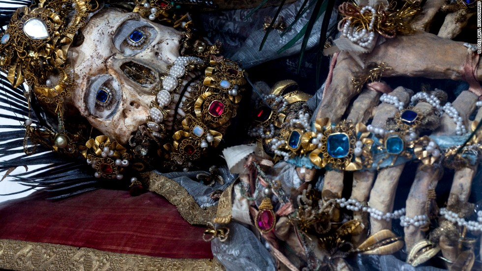 "<em>St. Valerius at rest in in Weyarn, Germany</em><br /><br />When archaeologists unlocked the catacombs of Rome in 1578, they unleashed a wave of religious fervor. Catholic officials disinterred skeletal remains, which they assumed to be early Christian martyrs, and had artisans reassemble them. Encrusted with gold and jewels, the skeletons then went on display in lavish shrines across Europe to convey the glory that awaited the Church's devout followers in the afterlife. But by the early 19th century their saintly authenticity came into question and, in a dramatic reversal of fortune, many of the relics were hidden from view or destroyed.<br /><br />Photographer and author Paul Koudounaris gained unprecedented access to these so-called ""catacomb saints"" for his new book <em><a href=""http://www.thamesandhudson.com/Heavenly_Bodies/9780500251959"" target=""_blank"">Heavenly Bodies</em></a><em>, </em>published by Thames and Hudson. Many had never been photographed for publication before. Revered as spiritual objects and then reviled as a source of embarrassment for the Church, their uneven history is marked by one constant: a mysterious, if unsettling, beauty. ""I wanted to pursue this project to provide a new context for them,"" Koudounaris says, ""and to look at them not as failed devotional items, but instead as fine objects of art.<br /><br />Interview by William Lee Adams"