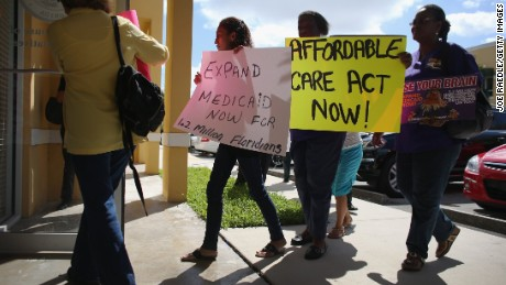 Demonstrators walk into a Florida state legislator's office to protest the state's stance against the expansion of Medicaid.