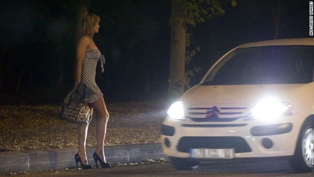 A prostitute waiting for customers stands on the sidewalk late on June 6, 2011 at the Bois de Boulogne park in Paris.