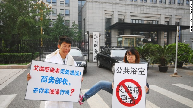 "Activist Liu Shi, left, stages a protest after a proposal to ban HIV/AIDS sufferers from entering bathhouses. His sign reads: ""HIV carriers have no place to bathe. Commerce minister, can we take a bath at your home?"""